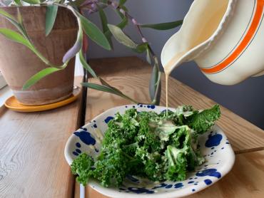 Vinaigrette bliver hældt ud af kande, henover grønkål som ligger i en smuk blå plettet tallerken