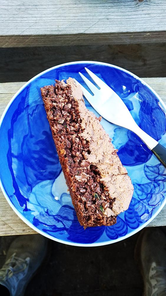 glutenfri squash kage med chokolade, fransk glasur med kokos. En smuk blå tallerken står med en skive kage lagt på siden sammen med en gaffel