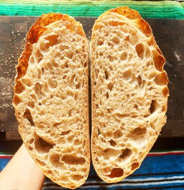 surdejsbrød bagt med smukke luft huller og smuk krumme, skåret halvt over og holdt op i mod hinanden med den flade side indad, baggrunden er mexikansk farvet stof