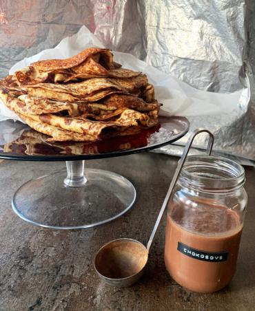 stor bunke af gyldende pandekager uden mel på højt fad med chokosovs i forgrunden i sylte glas