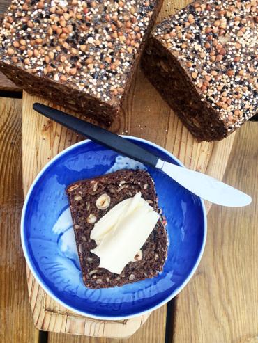 Rugbrød med hasselnødder, billedet er taget oppe fra og man ser rugbrødets top spækket med kerner og ved siden af en blå tallerken med en skive nybagt rugbrød med tandsmør